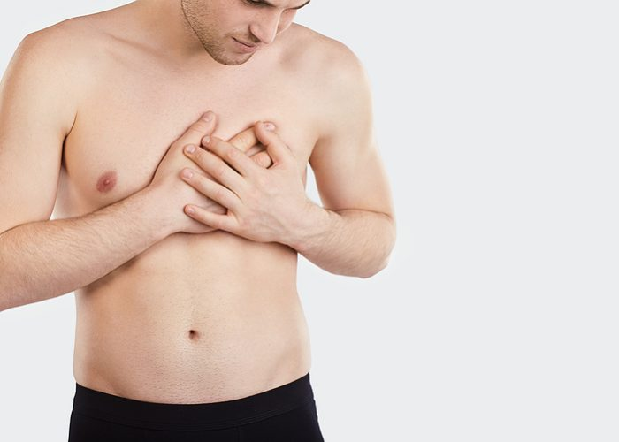 A man holds his chest with his hand