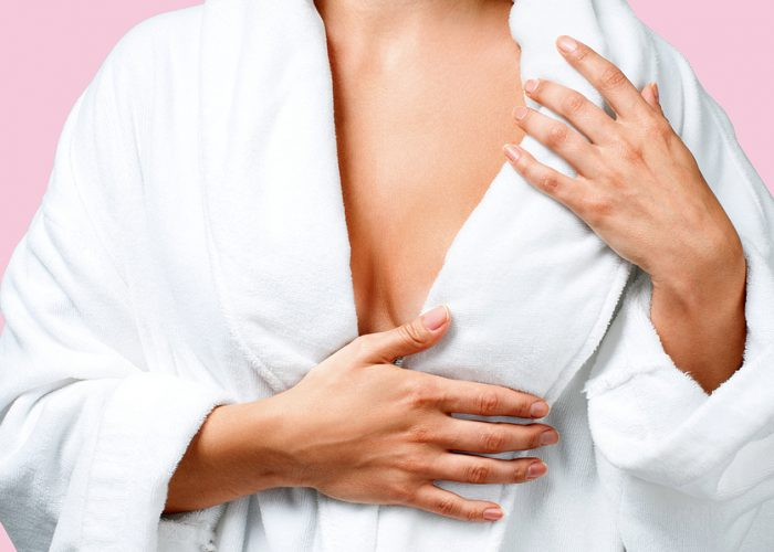Body care concept. Beautiful woman after bath in white bathrobe on pink background.