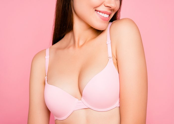 Cropped close up portrait of beautiful attractive gorgeous cute her she girl enjoying flawless perfect proportions decollete zone in pale pink bra isolated on pink background